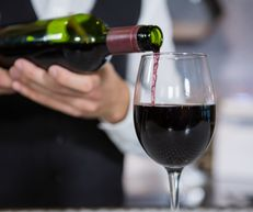 Mid section of bartender pouring red wine on glass in bar counter-2
