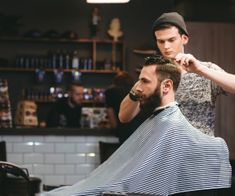 Young handsome barber making haircut of attractive bearded man in barb