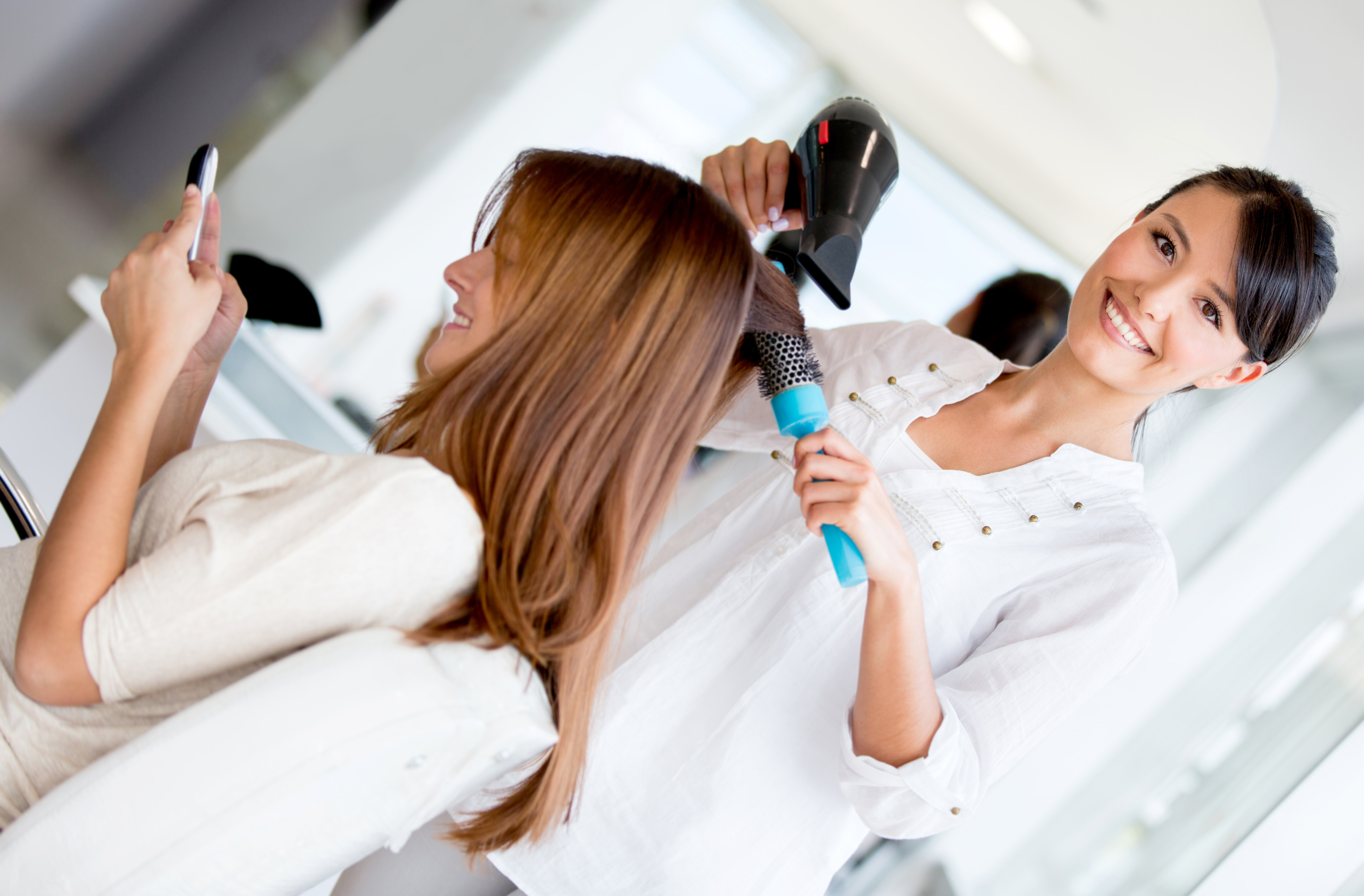 Hairdresser blowing woman's hair at the beauty salon